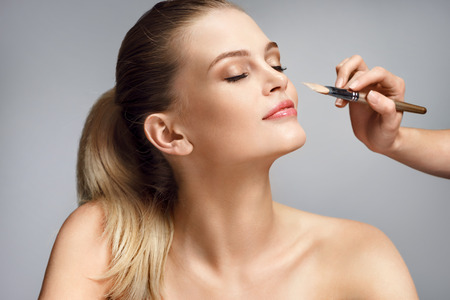 Beautiful woman applying liquid foundation on her face on grey background Stock Photo