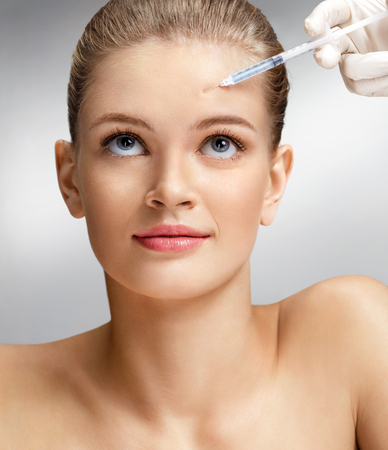 Beautiful woman face and beautician hands with syringe makes cosmetic injection in forehead. Clean Beauty concept