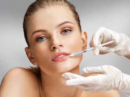 Beautiful woman face and beautician hands with syringe makes cosmetic injection in the upper lip. Clean Beauty concept Stock Photo