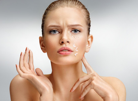 Upset woman touching her face. Photo of attractive woman with anti aging cream on grey background. Beauty & Skin care concept