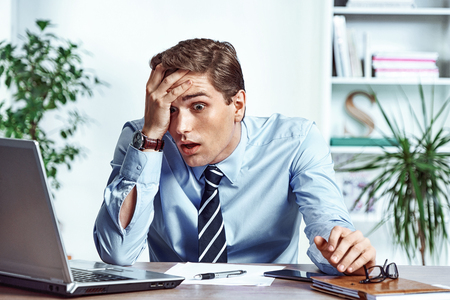 Shocked businessman dissatisfied his earnings. Photo of young man working in the office. Business concept Stock Photo