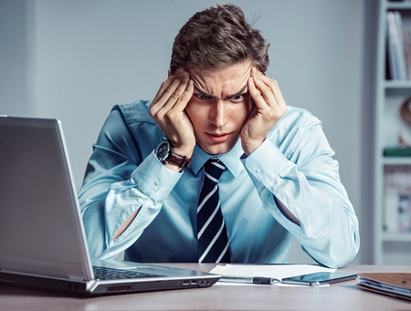 Young worker sitting in his office thinking. Business concept