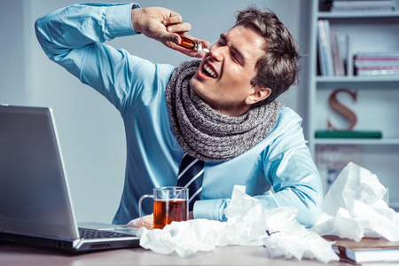 Sick employee using spray for nose. Photo of young man in office suffering virus of flu. Medical concept. Banco de Imagens