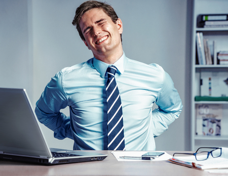 Employee suffers from severe pain in back. Photo of man working in the office. Medical concept. Stock fotó - 103368249