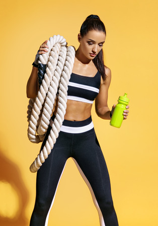 Beautiful strong woman with heavy ropes on her shoulders and holding shaker. Photo of muscular woman in fashionable sportswear on yellow background. Health concept.