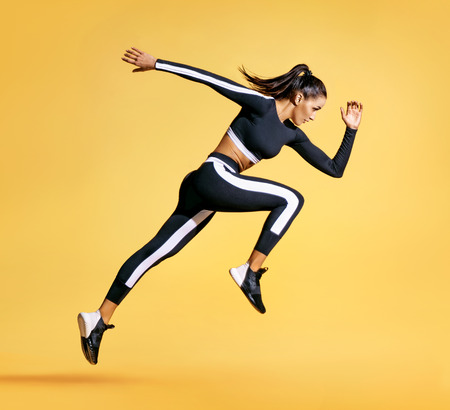 Sportlicher Frauenläufer in der Schattenbild auf gelbem Hintergrund. Foto der attraktiven Frau in der modischen Sportbekleidung. Dynamische Bewegung. Seitenansicht. Sport und gesunder Lebensstil Standard-Bild