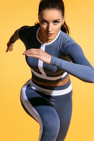 노란색 바탕에 유행 운동복에 매력적인 여자 주자. 역동적 인 움직임. 확대. 스포츠와 건강한 라이프 스타일