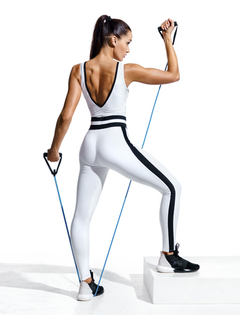 Fitness girl performs exercising with resistance band. Photo of sporty girl in fashionable sportswear isolated on white background. Strength and motivation. Full length