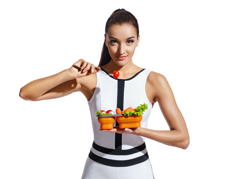 Sporty girl holding container with healthy nutrition. Photo of fitness model in fashionable sportswear isolated on white background. Healthy nutrition