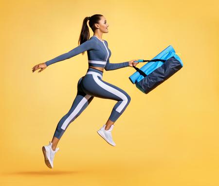 Ga naar training. Sportieve vrouw met zak die in silhouet op gele achtergrond loopt. Dynamische beweging. Zijaanzicht. Sport en een gezonde levensstijl