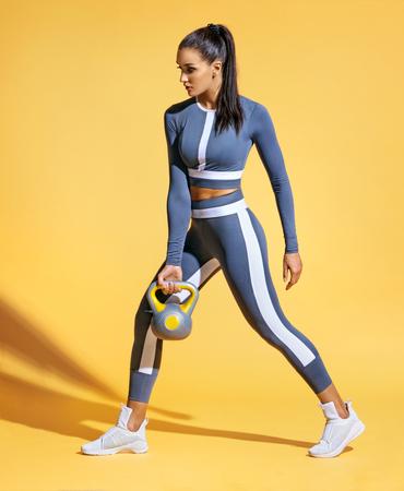 Donna sportiva che allena i muscoli delle mani e delle gambe utilizzando un kettlebell. Foto di una donna latina in abiti sportivi alla moda su sfondo giallo. Forza e motivazione.