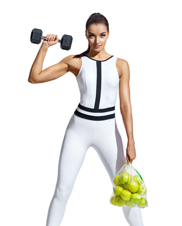 Strong woman with dumbbell and bag of apples. Photo of muscular woman in fashionable sportswear on white background. Healthy lifestyle and motivation