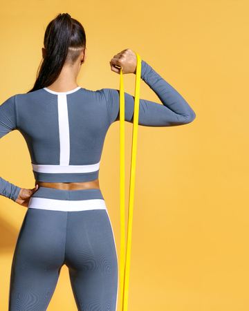 Fitness girl performs exercises for the muscles of the hands with resistance band. Photo of latin girl in fashionable sportswear on yellow background. Strength and motivation. Rear view Banco de Imagens