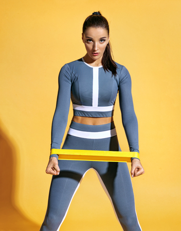 Sporty woman performs exercises for the muscles of the hands. Photo of woman workout with resistance band on yellow background. Strength and motivation.