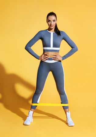 Attractive sportswoman performs exercises with resistance band. Photo of latin woman in fashionable sportswear on yellow background. Strength and motivation.