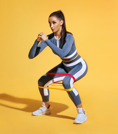 Sporty woman squatting doing sit-ups with resistance band. Photo of latin woman in fashionable sportswear on yellow background. Strength and motivation.