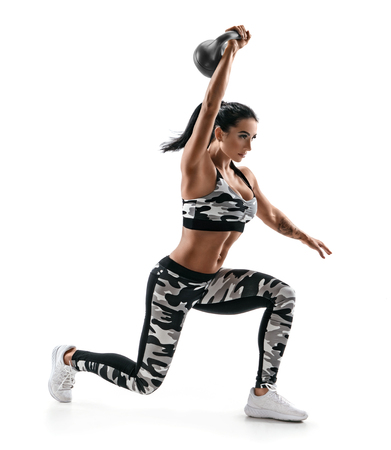 Strong woman training muscles of hands and legs using a kettlebell. Photo of attractive woman in fashionable sportswear isolated on white background. Strength and motivation