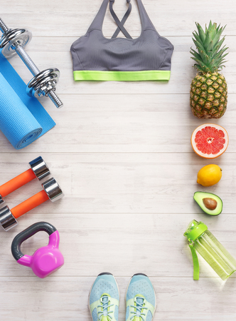 Sports equipment and healthy food on a white wooden background. Top view. Motivation. Copy space