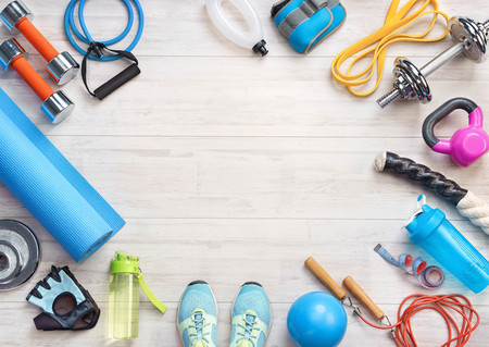 Sports equipment on a white wooden background. Top view. Motivation. Ð¡opy space.