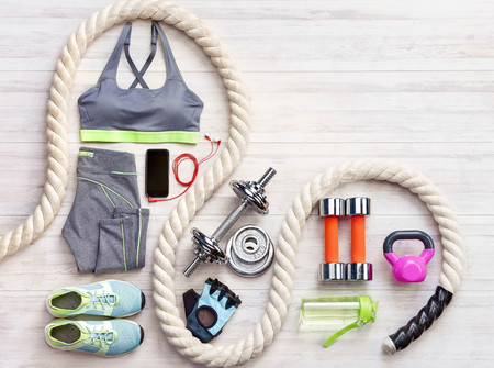 Sports equipment on a white wooden background. Top view. Motivation
