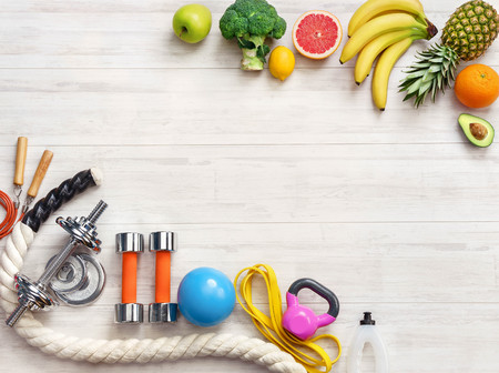 Sports equipment and healthy food on a white wooden background. Top view. Motivation. Ð¡opy space.