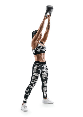 Sporty latin woman doing kettlebell swings. Photo of woman with good physique in fashionable sportswear isolated on white background. Strength and motivation. Full length