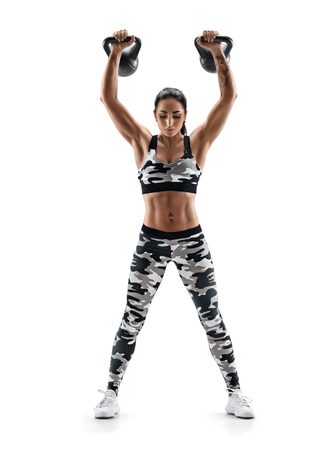Sportswoman working out with kettlebell. Photo of latin woman with good physique in fashionable sportswear isolated on white background. Strength and motivation. Full length