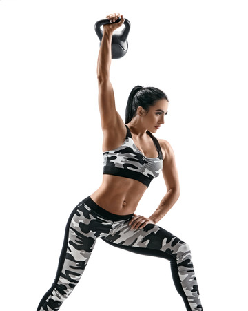 Fitness woman working out with kettlebell. Photo of woman with good physique in fashionable sportswear isolated on white background. Strength and motivation Reklamní fotografie