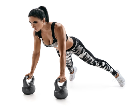 Athletic woman doing push ups exercise with kettlebells. Photo of latin woman in fashionable sportswear isolated on white background. Strength and motivation