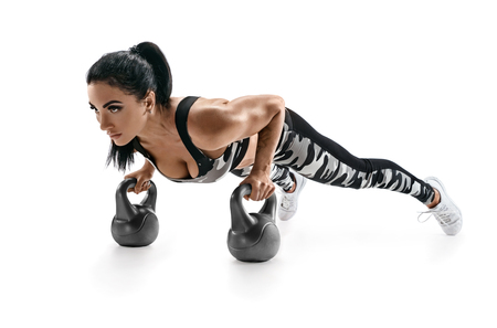 Sporty woman doing push ups exercise with  kettlebells. Photo of latin woman in fashionable sportswear isolated on white background. Strength and motivation
