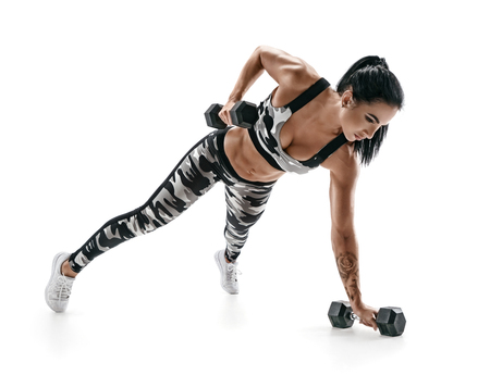 Beautiful athletic woman doing exercise with dumbbells. Photo of sporty latin woman in military sportswear isolated on white background. Strength and motivation.