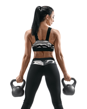 Muscular back of woman. Rear view of fitness model with kettlebells isolated on white background. Strength and motivation.