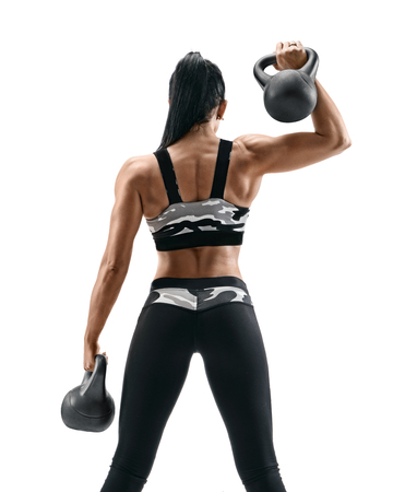 Sporty woman doing exercises with kettlebells. Rear view of latin woman with athletic body isolated on white background. Strength and motivation