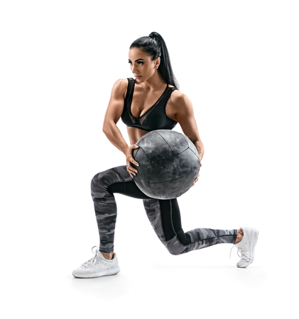 Muscular woman doing lunge twist exercise with med ball. Photo of woman with great physique isolated on white background. Strength and motivation