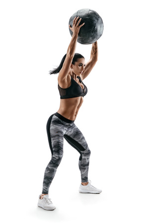 Strong woman doing exercise with med ball. Photo of latin woman in fashionable sportswear isolated on white background. Strength and motivation.