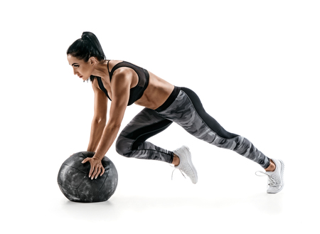 Strong woman workout with medicine ball. Photo of latin woman in military sportswear isolated on white background. Strength and motivation.