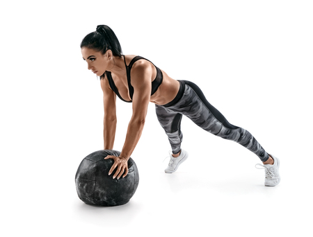 Sporty latin woman doing push ups on med ball. Photo of woman in military sportswear isolated on white background. Strength and motivation Reklamní fotografie