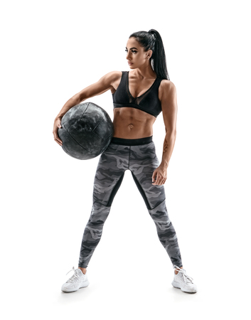 Strong woman holding med ball. Photo of sporty latin woman with great physique isolated on white background. Strength and motivation. Full length