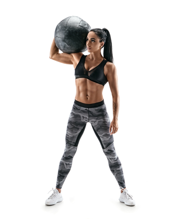 Athletic woman holding med ball on her shoulder. Photo of sporty model with great physique isolated on white background. Strength and motivation. Full length