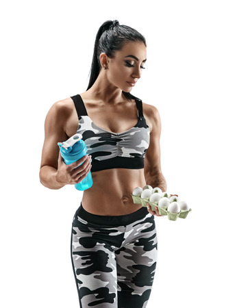 Sporty woman holding container with chickens eggs and protein cocktail in shaker. Photo of attractive woman in military sportswear on white background. Healthy lifestyle. Reklamní fotografie