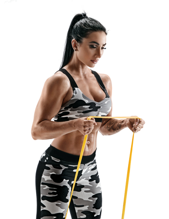 Beautiful strong model performs exercises using a resistance band. Photo of latin woman in military sportswear isolated on white background. Strength and motivation