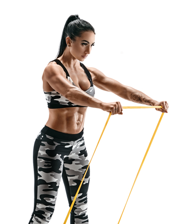 Attractive muscular woman performs exercises using a resistance band. Photo of sporty woman in military sportswear isolated on white background. Strength and motivation