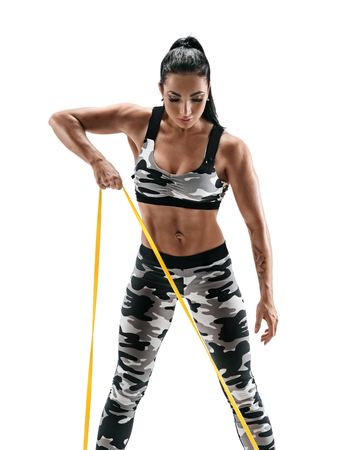 Woman with beautiful athletic body performs exercises using a resistance band. Photo of latin woman in military sportswear isolated on white background. Strength and motivation Reklamní fotografie