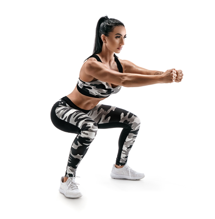 Sporty woman doing squats. Photo of muscular fitness model in military sportswear isolated on white background. Fitness and healthy lifestyle concept