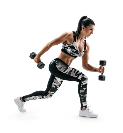 Sporty woman training muscles of hands and legs using a dumbbells. Photo of muscular latin woman in military sportswear isolated on white background. Strength and motivation. Side view Reklamní fotografie