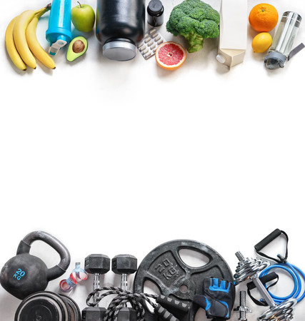Sports equipment and organic food on a white background. Top view. Motivation. Copy space.