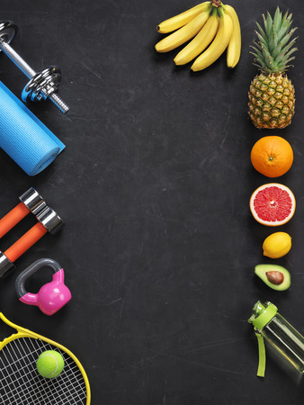 Sports equipment and organic food on black background. Top view. Motivation