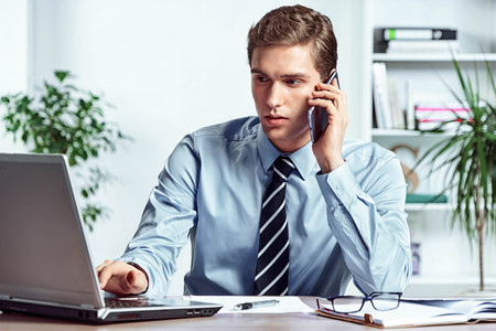 Worker talking on the phone and looks at the laptop. Photo of successful manager working with financial data in the office. Business concept