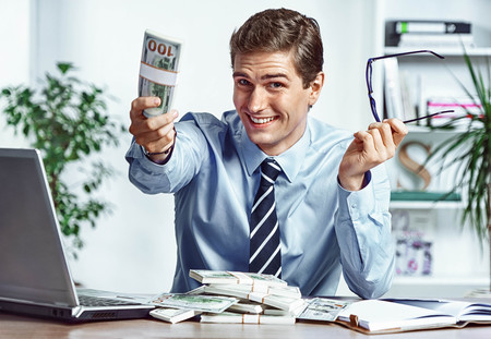 Successful businessman takes off his glasses and showing money. Photo of young man working in the office. Business concept Reklamní fotografie