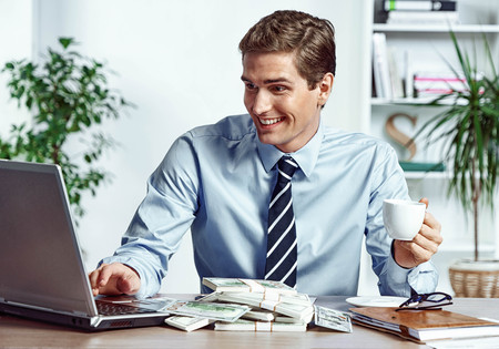 Worker looking at the laptop and drinking coffee. Photo of happy young man working in the office. Business concept